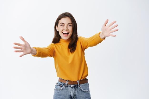 幸せな笑顔の女性はゲストを迎えるために手を伸ばし、抱擁またはあなたを歓迎したい