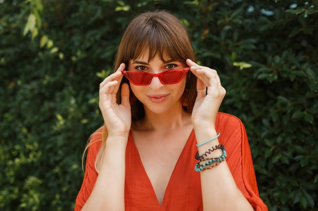 Happy smiling woman in stylish red sunglasses and orange dress posing outdoor over tropical garden.