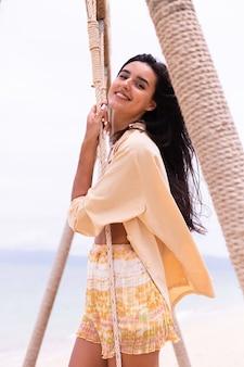 Donna sorridente felice su oscillazione in spiaggia, luce calda del giorno.
