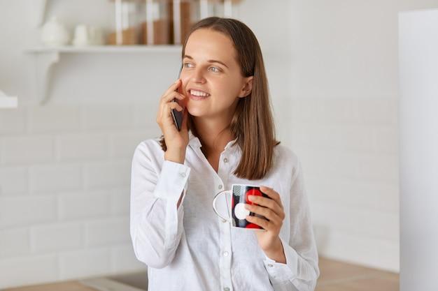 目を覚ました後、温かい飲み物を飲み、コーヒーやお茶を楽しみ、楽観的な表情で目をそらした後、朝に電話を話している幸せな笑顔の女性。