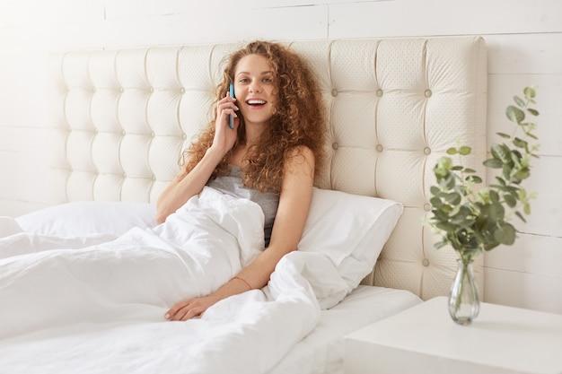 Счастливая улыбающаяся женщина разговаривает по смартфону