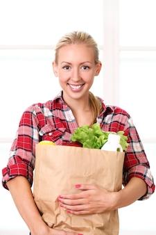 Счастливая усмехаясь женщина с продуктовой сумкой