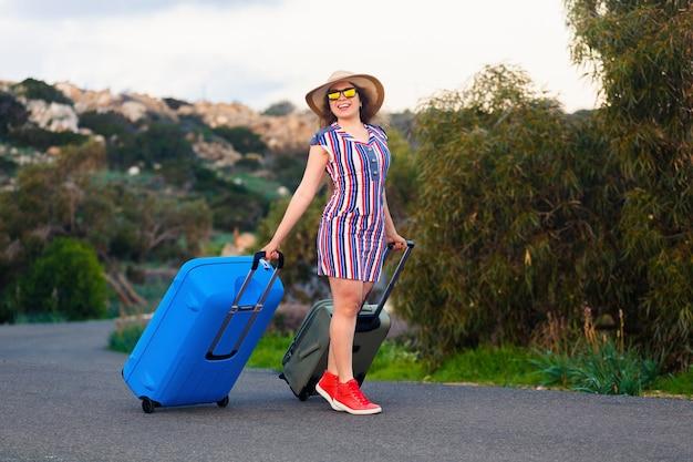 道路上の青いスーツケースと幸せな笑顔の女性。