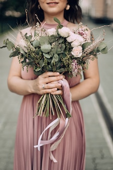 Happy and smiling woman with bouquet of flowers in a pink wedding dress and wedding ring