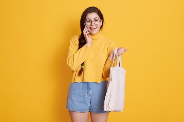 黒い髪とピグテールが黄色の壁にポーズをとって電話で話し、綿の袋を手に持って、短いセーターとジーンズを着て幸せな笑顔の女性。