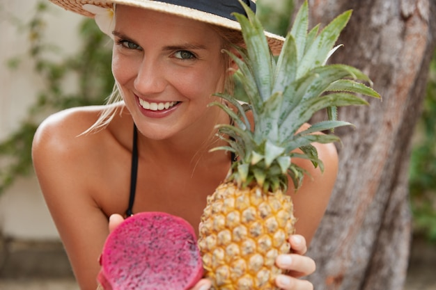 Happy smiling woman with healthy skin, has broad smile, eats exotic fruits, has good recreation in tropical country, spends summer vacation in paradise place, recieves vitamins. healthy eating