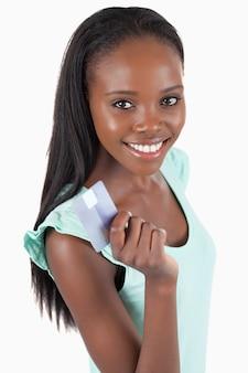 Счастливый улыбается женщина с ее кредитной карты на белом фоне