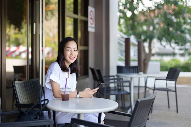 Happy smiling woman with iced coffee and cell phone sitting on cafe terrace outdoors.