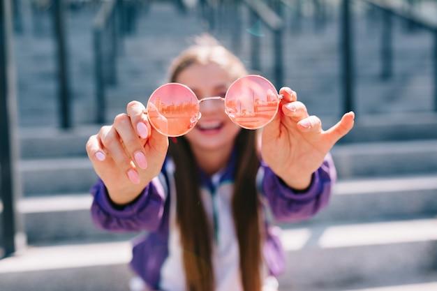 長い髪の幸せな笑顔の女性はピンクのメガネを保持している明るいジャケットを着て、外で楽しんでいます
