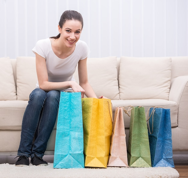 Happy smiling woman with shopping bags on the couch.