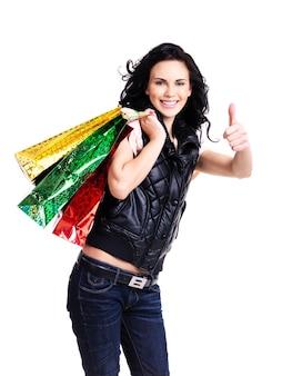 La donna sorridente felice con i sacchetti della spesa mostra i pollici sul segno isolato su fondo bianco.