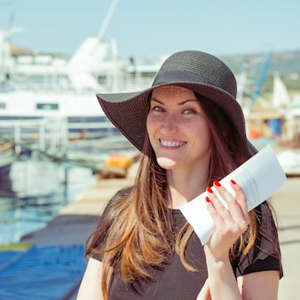 Happy smiling woman with tickets for the cruise at the port resort city.