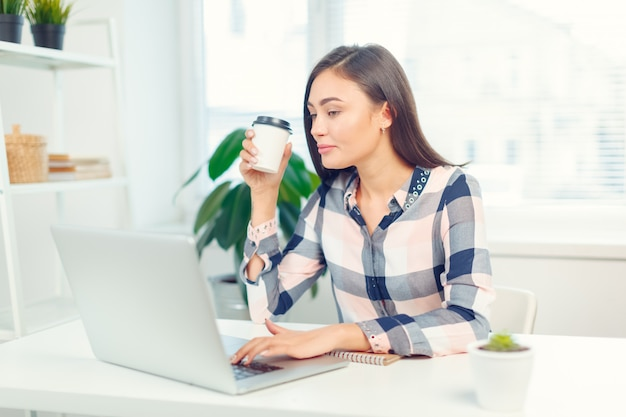 Happy smiling woman working with laptop and drinking coffee
