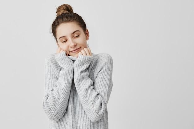 Счастливая усмехаясь женщина оборачивая ее лицо в воротнике серого свитера. женщина милашка чувствует себя комфортно и тепло с удовольствием закрывает глаза. концепция гармонии