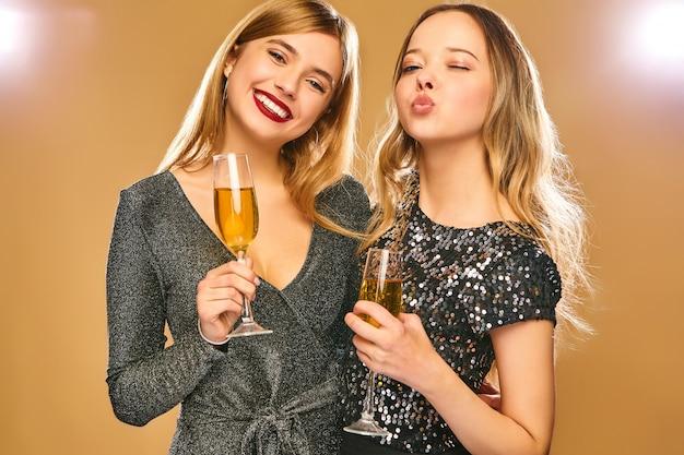 황금 벽에 샴페인 안경 세련된 매력적인 드레스에 행복 웃는 여자