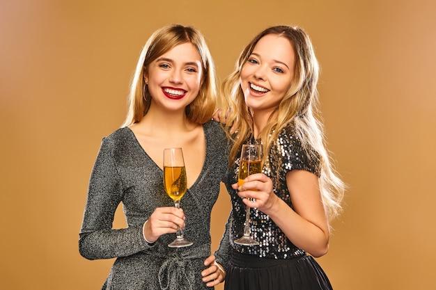 シャンパングラスとスタイリッシュな魅力的なドレスで幸せな笑顔の女性