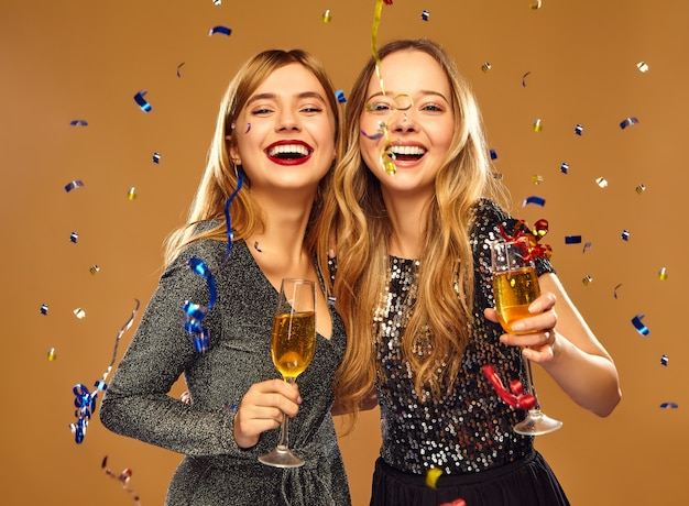 Happy smiling women in stylish glamorous dresses with champagne glasses under confetti