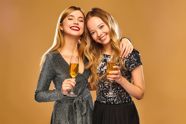 Happy smiling women in stylish glamorous dresses with champagne glasses on golden wall