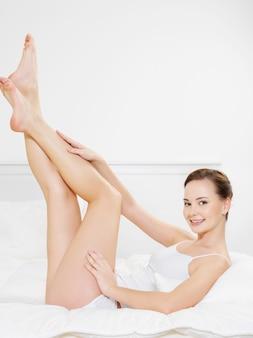 Giovane donna adulta sorridente felice con belle gambe sdraiato sul letto - al chiuso