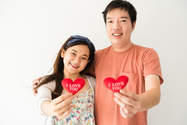 Happy smiling young asian couple's hands holding red fake heart with i love you text with copy space on white background. 2021 valentine day celebration.