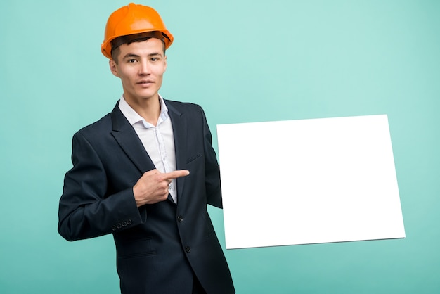 Happy smiling young asian engineer man points finger blank signboard on blue background
