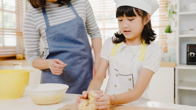 Happy smiling young asian japanese family with preschool kids have fun cooking baking pastry
