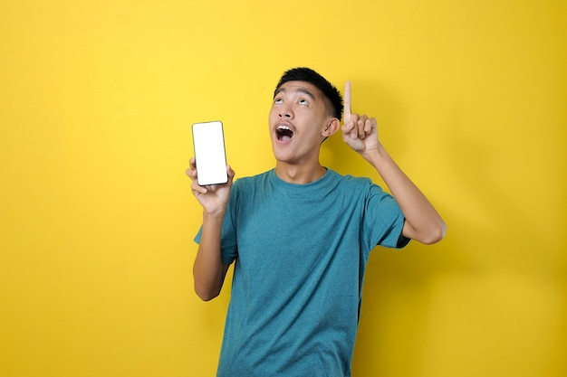 Happy smiling young asian man showing mobile phone with another hand pointing to empty space on colorful yellow background