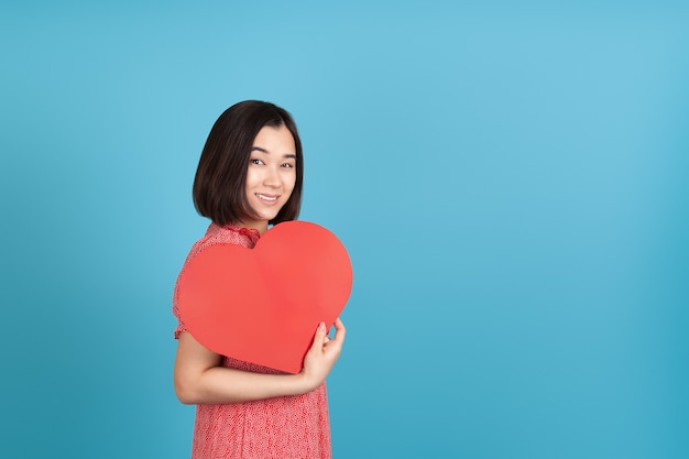 Счастливая, улыбающаяся молодая азиатская женщина в красном платье держит большое красное бумажное сердце как вентилятор