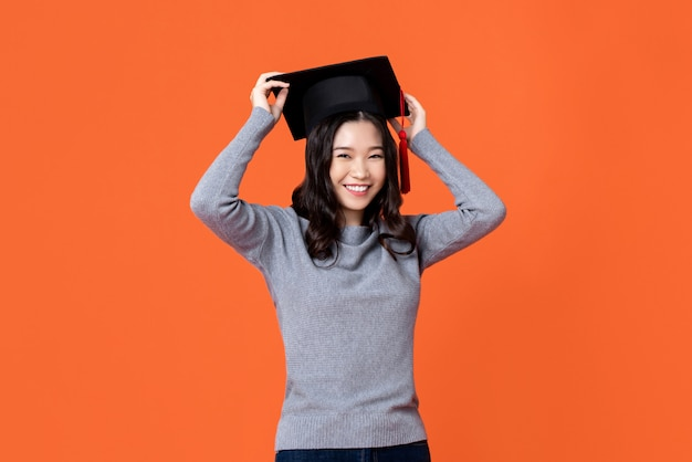 Happy smiling young asian woman wearing graduation cap