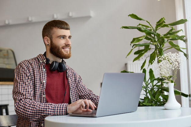Happy smiling young attractive ginger bearded man sits at a table in a cafe and works on a laptop, wearing in basic clothes, looking away.