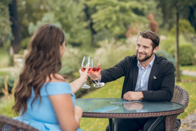 Happy smiling young bearded man in black suit and white shirt with glass of wine and woman from back in outdoor cafe