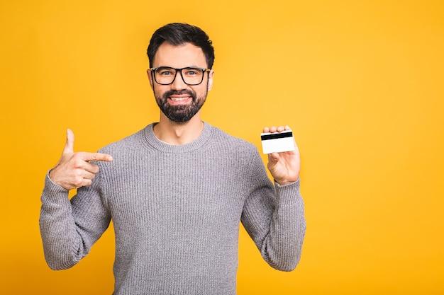 黄色の背景で隔離のクレジットカードを保持している幸せな笑顔の若いひげを生やした男。