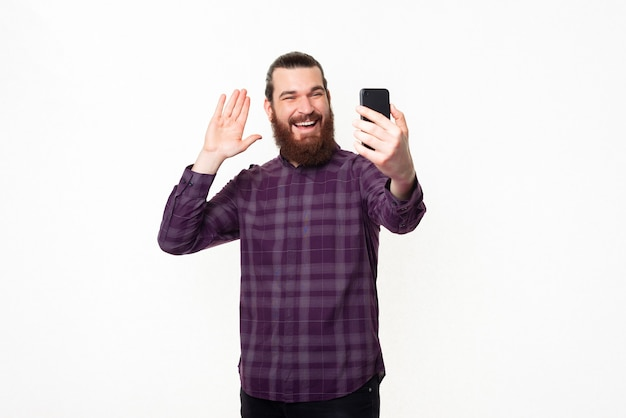 Happy smiling young bearded man talking to someone with smartphone and saluting