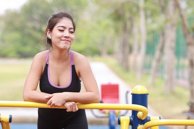 운동복 차림으로 웃고 있는 아름다운 아시아 여성이 공공 운동 기계에서 휴식을 취하고 있습니다. 귀엽고 스포티한 소녀는 여름 야외에서 아침 운동을 하는 동안 이어폰과 모바일을 통해 음악을 듣습니다.