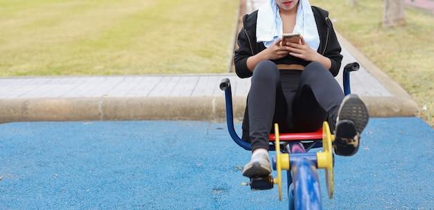 운동복 차림으로 웃고 있는 아름다운 아시아 여성이 공공 운동 기계에서 휴식을 취하고 있습니다. 자전거로 운동하고 야외에서 모바일 스마트폰을 사용하는 귀엽고 스포티한 소녀
