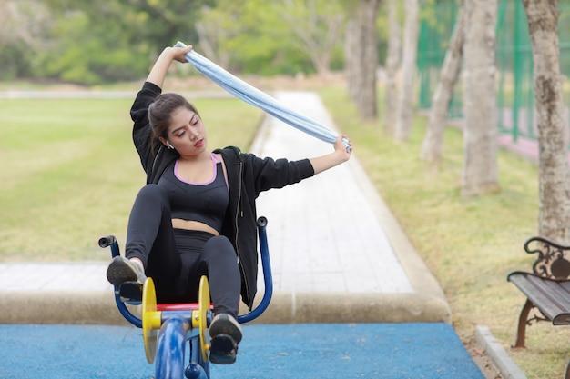 운동복 차림으로 웃고 있는 아름다운 아시아 여성이 공공 운동 기계에서 휴식을 취하고 있습니다. 여름 야외에서 아침에 자전거를 타고 운동하는 귀엽고 스포티한 소녀.