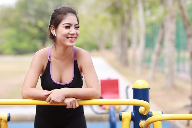 Счастливая улыбающаяся молодая красивая азиатская женщина в спортивной одежде, расслабляющаяся на общественном тренажере