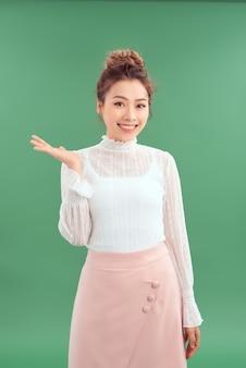 幸せな笑顔の若い美しいビジネス女性は、緑の背景で隔離の製品やサインテキストの何かまたはcopyspaseを示しています。