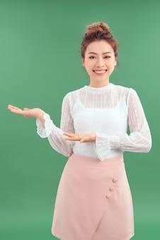 Счастливая улыбающаяся молодая красивая деловая женщина, показывающая что-то или copyspase для продукта или подписывающего текста, изолированная на зеленом фоне