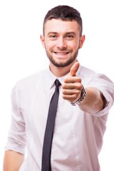 흰 벽에 고립 된 제스처를 엄지 손가락으로 행복 하 게 웃는 젊은 비즈니스 맨