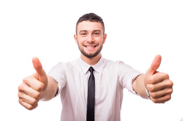 Счастливый улыбающийся молодой деловой человек с большими пальцами руки вверх жест, изолированные на белой стене