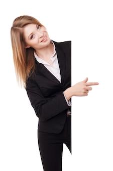 Счастливая улыбающаяся молодая деловая женщина, показывающая пустую вывеску, изолированную на белом фоне