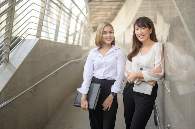 幸せな笑顔の若いビジネス女性は、ビジネスプランについて話している現代の都市で働いています