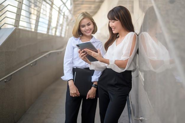 Счастливые улыбающиеся молодые деловые женщины работают в современном городе, обсуждая бизнес-план