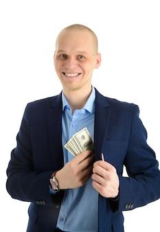 Счастливый улыбающийся молодой предприниматель, положив деньги в карман своего костюма
