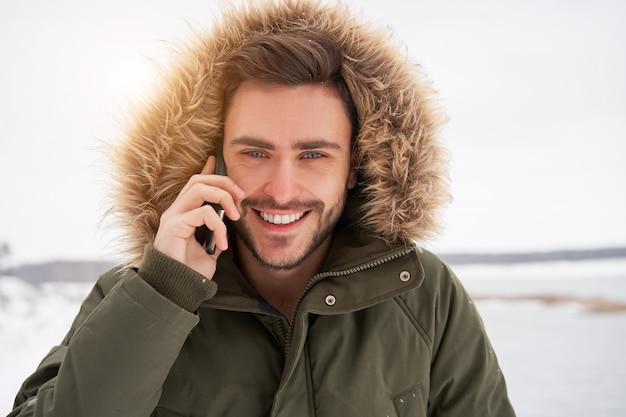 Счастливый улыбающийся молодой человек кавказской разговаривает по телефону зима