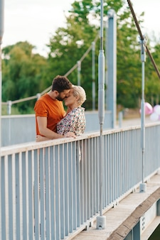 Happy smiling young couple hugging and kissing on bridge
