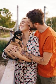 Giovani coppie sorridenti felici che abbracciano il loro cane sul ponte