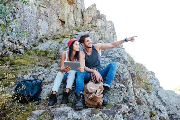 山でハイキングしながらタブレットコンピューターで休んで幸せな笑顔の若いカップル