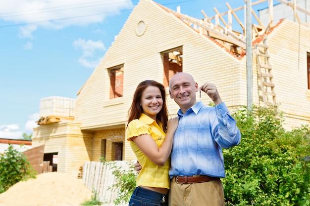 Счастливая улыбающаяся молодая пара, показывающая пару ключей от своего нового дома